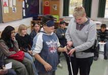 Petra Schneider zeigt dem Schüler Ener, wie es ist, blind zu sein. FOTO: MARTIN KALB